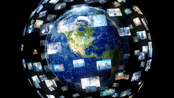 Earth surrounded by video screens of people