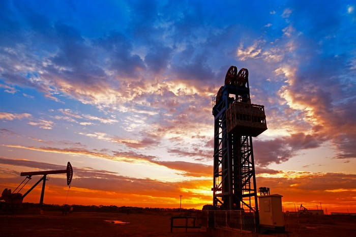An oil drilling rig and pump jack at sunset.