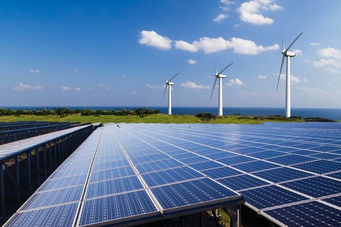 Solar panels alongside a wind farm.