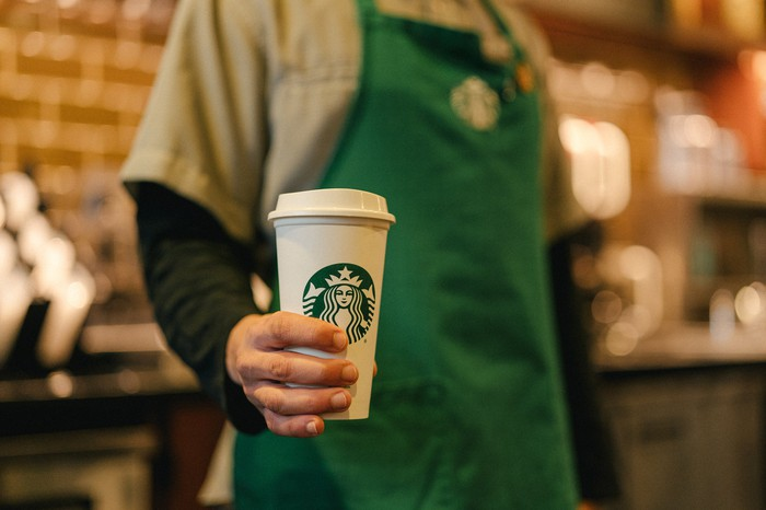 A Starbucks employee holds a to-go cup of coffee.