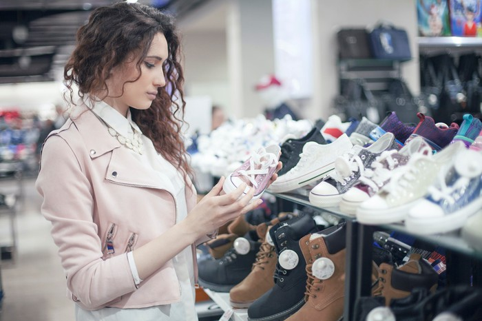 A woman inspects a sneaker in a shoe store.