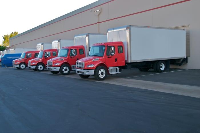 Semi-trucks backed up to loading bays at a fulfillment warehouse.