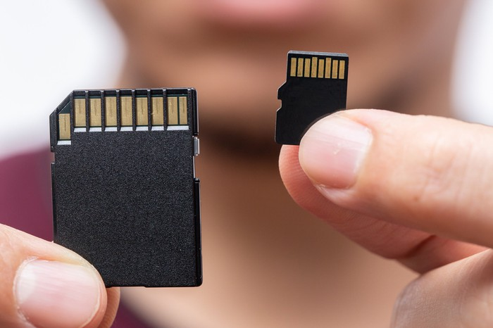 One tablet memory chip and one smartphone memory chip, each held by two fingers.