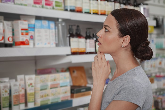 A woman shopping for medicine in a store aisle