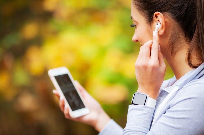 A woman putting in her wireless earphones.