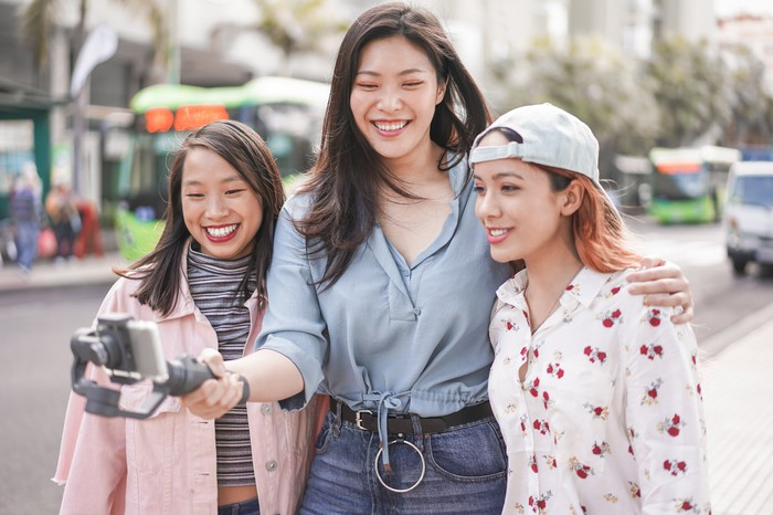 Three young women stream a live video outside.