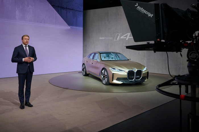 Zipse is shown on a stage with the BMW i4 concept car, an electric sedan.