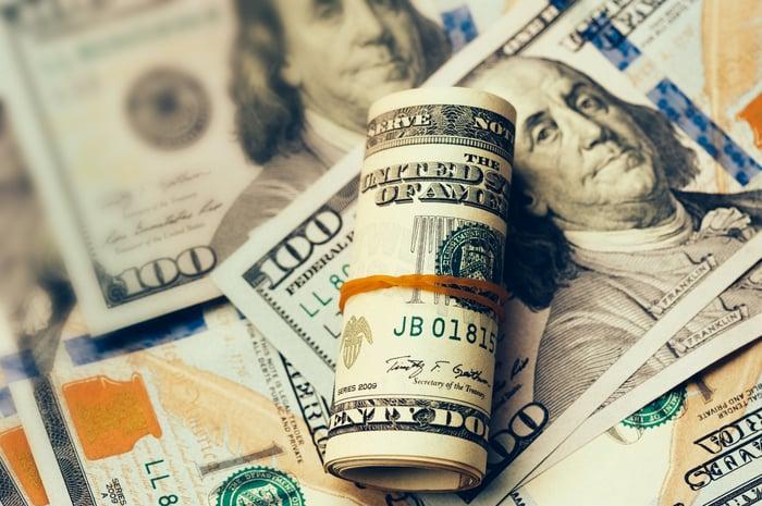 A wad of twenty dollar bills sitting atop several hundred dollar bills.