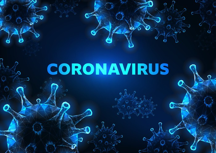 Surrounded by an artist's rendering of disease cells, the word coronavirus glows in blue.