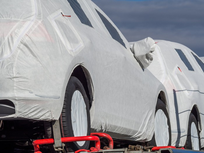 Produced cars covered in white, waiting to move from manufacturer