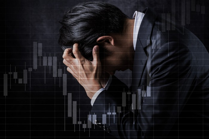 A roller coaster stock chart superimposed over a man with his head in his hands.