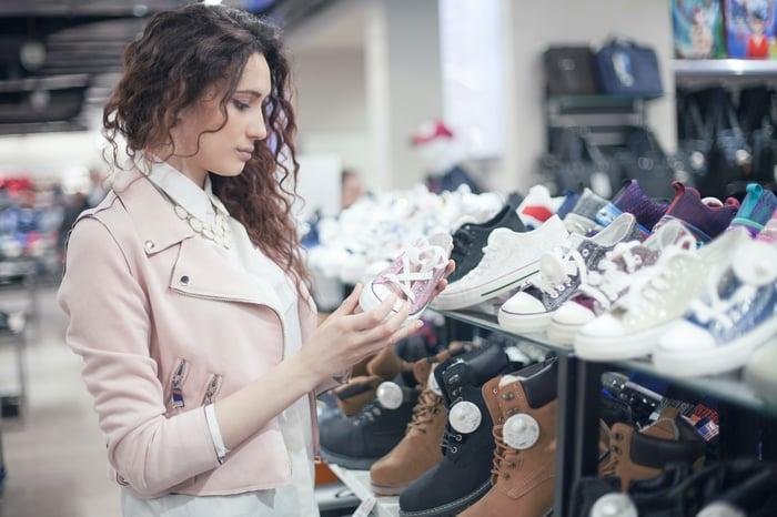 A woman inspects a sneaker in a shoe store.