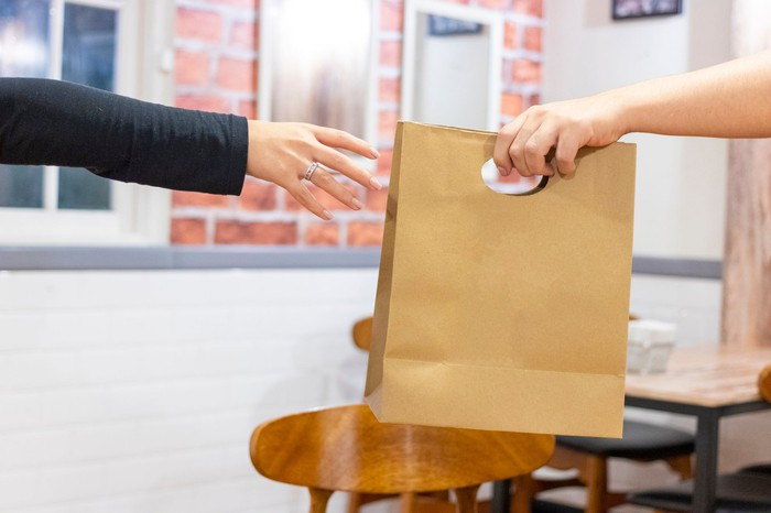 Person getting a take-out bag.
