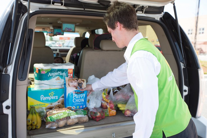 A man in a Walmart vest loading groceries into the trunk of a car.