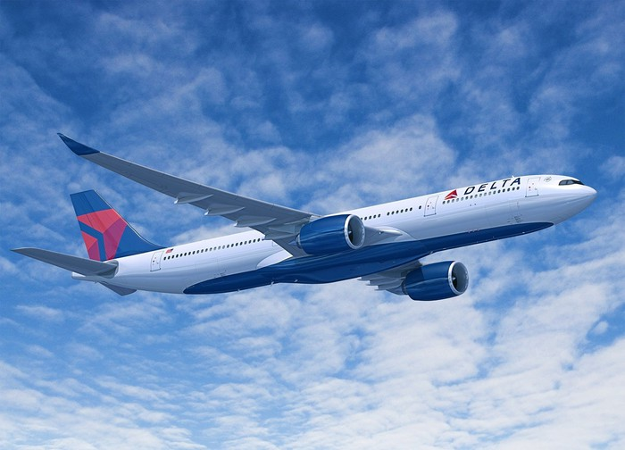 Delta aircraft in flight against a partly cloudy blue sky.
