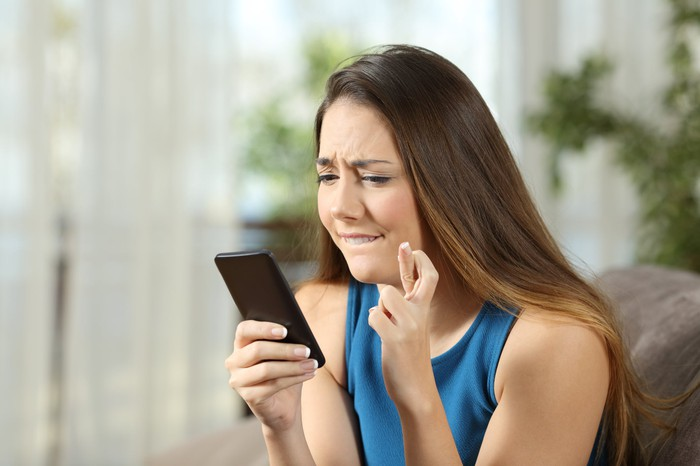 A young woman crosses her fingers and bites her lip while frowning at her smartphone.