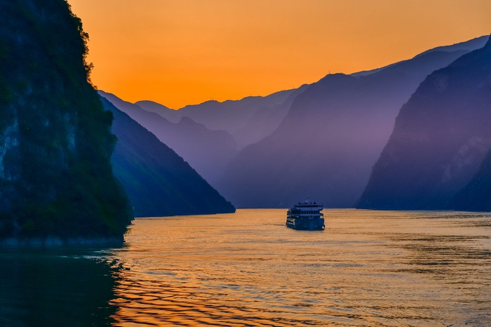 A cruise ship goes into a river surrounded by mountains at sunset.