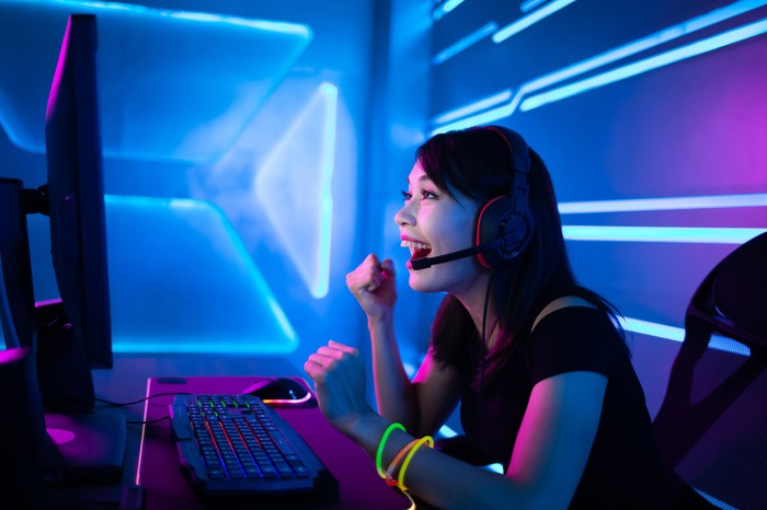 A woman plays a PC game on her computer and smiles with blue lights flashing around her.