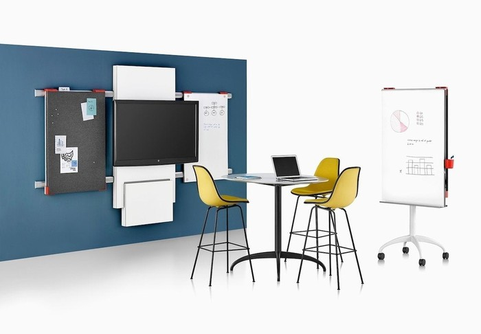 Contemporary table and chairs surrounded by whiteboards and other workplace collaboration tools.