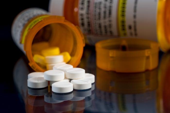 Pills spilling out of a prescription bottle.