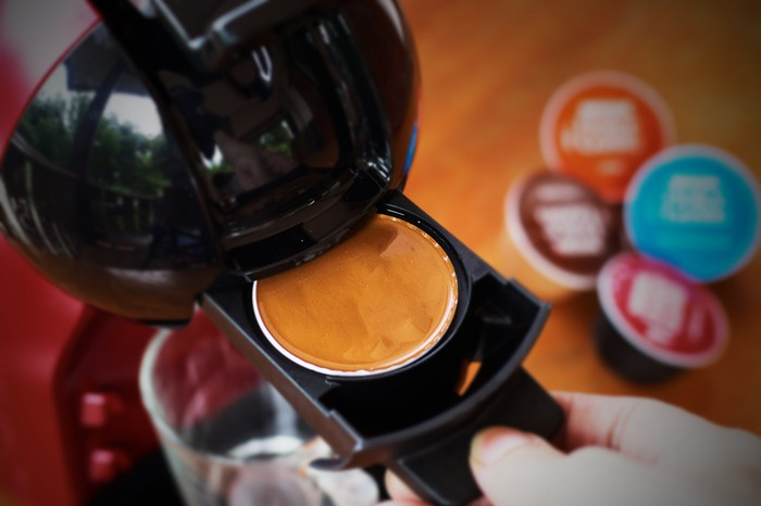 """A home coffee maker is pictured with numerous coffee pods or """"K-cups"""" nearby."""