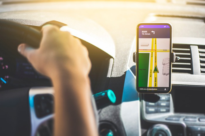 A person driving a car. A smart-device displaying directions is on the dash.
