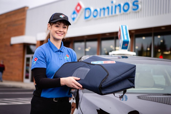 A Domino's delivery driver holds a pizza warmer.