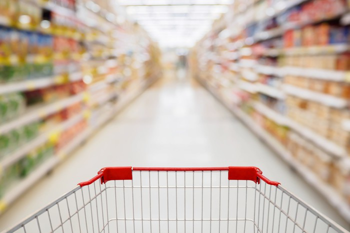 The front of a shopping cart viewed from the back in a grocery store aisle with shelves full of food products.