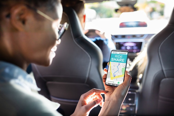 Image of man holding a smartphone with ridesharing app displayed.