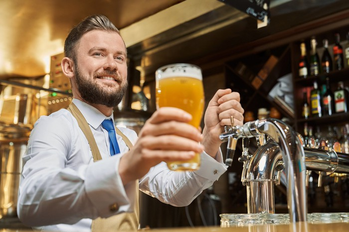 Man behind bar holding glass of beer