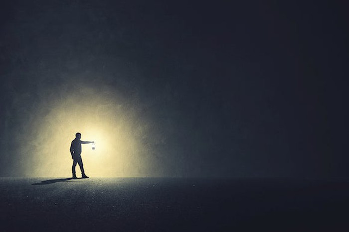 Man holding a bright light in a dark room
