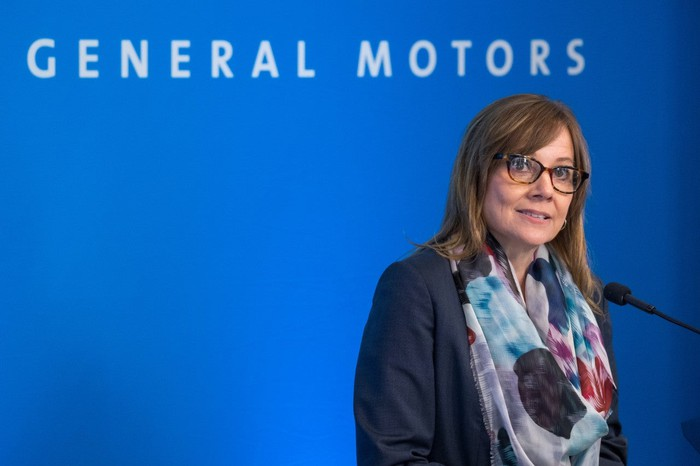 GM CEO Mary Barra stands in front of a General Motors press backfrop.