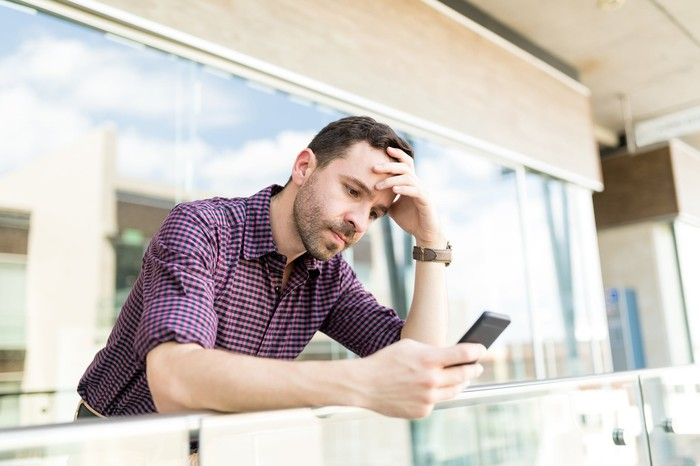 Man with serious expression holding head while looking at cell phone