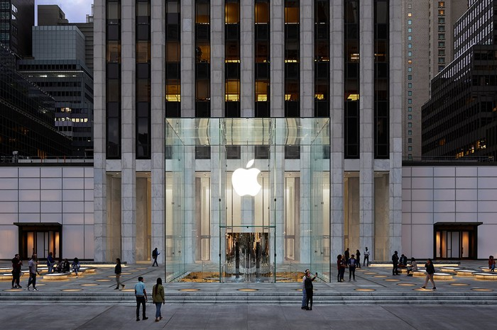 The Apple logo lit up at dusk at its 5th Avenue store in New York.