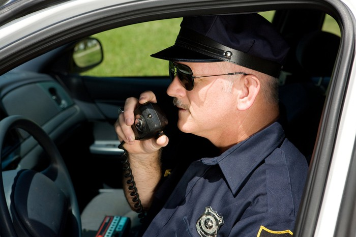 A policeman speaks on a CB radio while in his car.