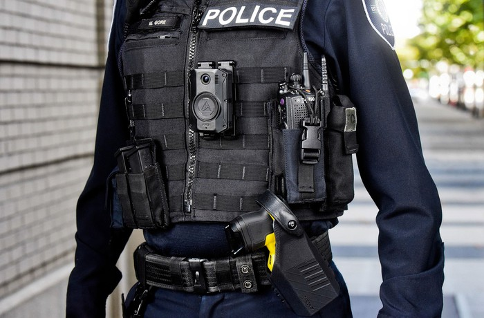 Police officer wearing vest, Body 3 camera, and signal sidearm holster while patrolling the street.