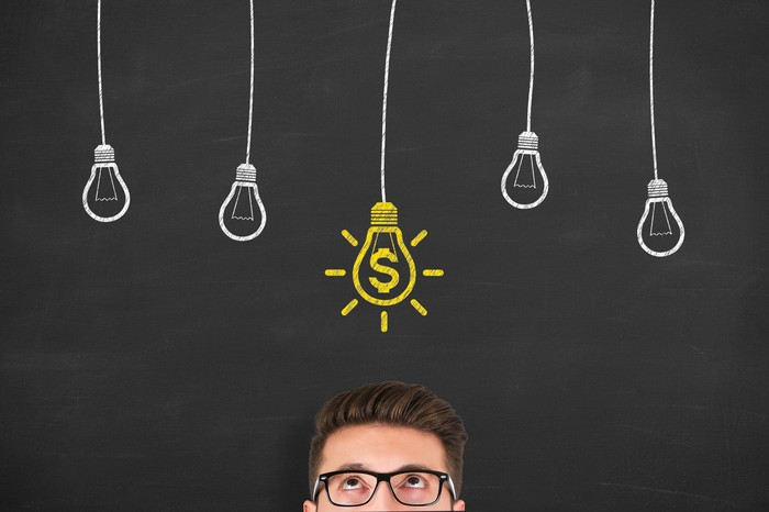 Man wearing glasses looking up at a chalkboard drawing of light bulbs with one light bulb colored in yellow with a dollar sign in it