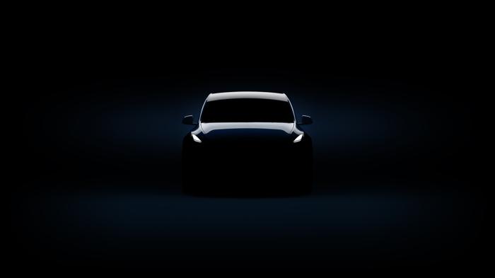 A Tesla Model Y, in a dark room.