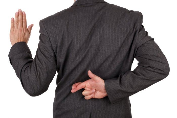 A businessman facing away from the viewer, holding one hand up while crossing his fingers on the other one behind his back.