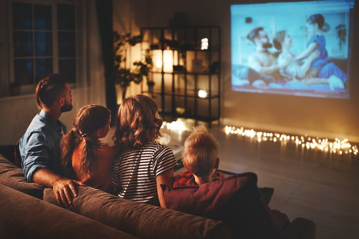 A family of four sitting on a couch together watching a movie.