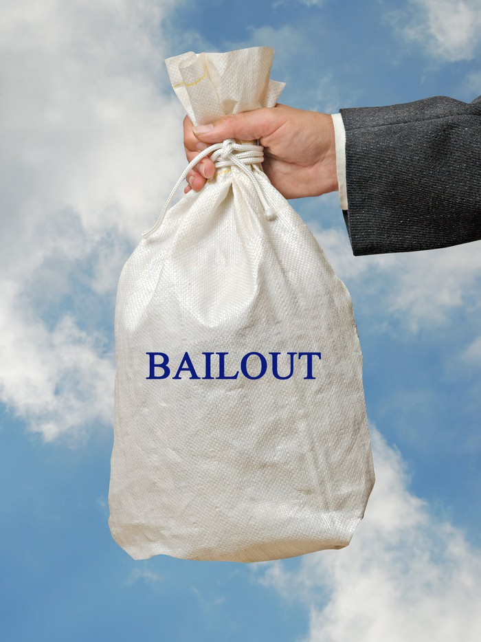 Official handing bag of money labeled bailout