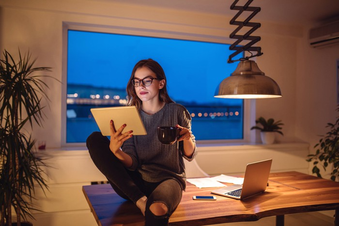Young woman works from home drinking coffee sitting on a desk and reading from a tablet PC