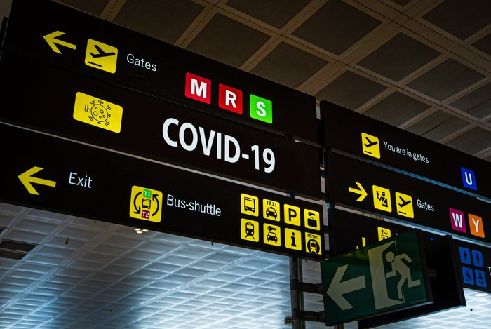 Information panel at an airport with COVID-19 on it.