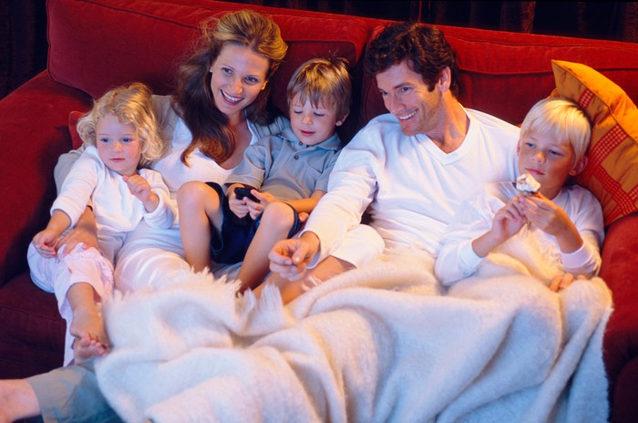 A young couple with three young children sitting on the couch, watching television while covered in blankets.