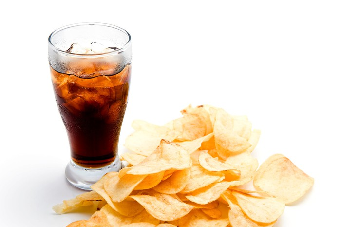 Glass filled with ice and cola next to some potato chips