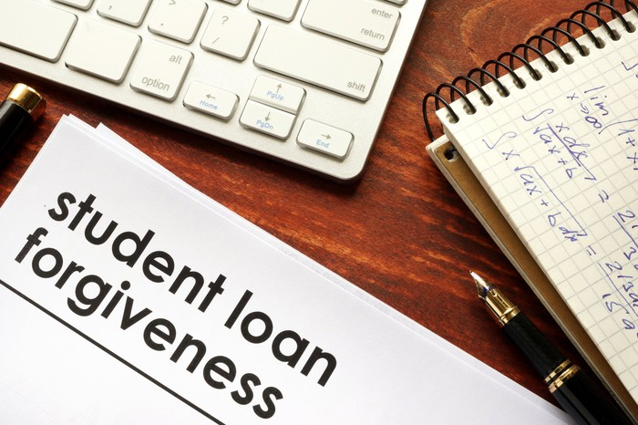 An image of a desktop with a paper on it that says Student Loan Forgiveness.