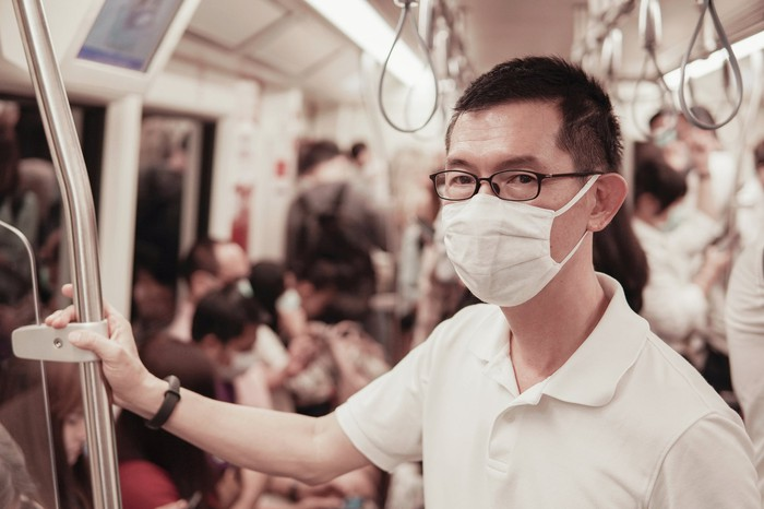 A man on a crowded subway train wearing a surgical face mask.
