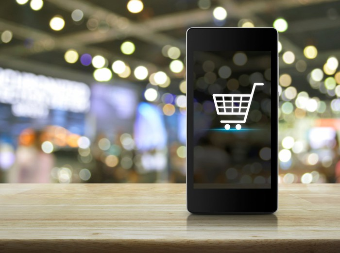 Shopping cart icon on smartphone screen over blurred-out mall