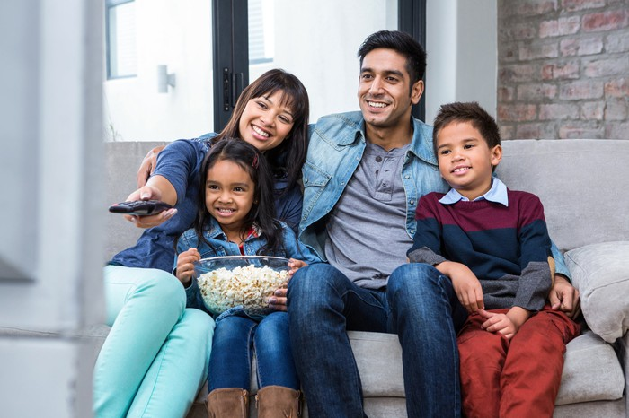 A young couple with two children sitting on the couch with popcorn and the remote watching television.