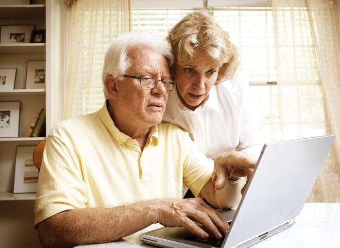 An elderly couple sharing a laptop.